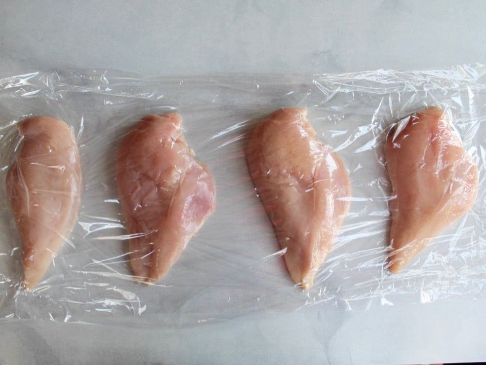 4 chicken breasts sandwiched between two layers of plastic wrap on countertop, spaced a couple of inches apart.