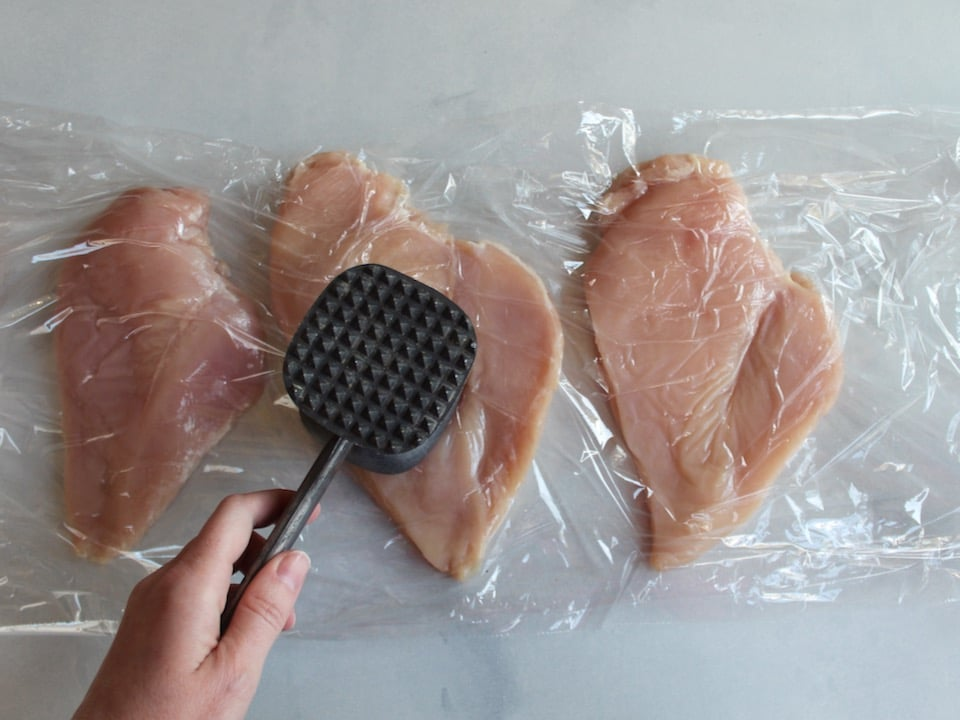 Hand pounding out chicken breasts between layers of plastic wrap with a metal mallet.