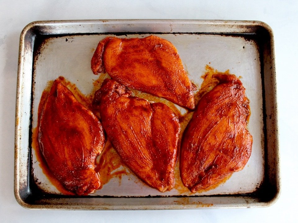 4 flat pounded chicken breasts brushed with paprika marinade on a baking sheet.