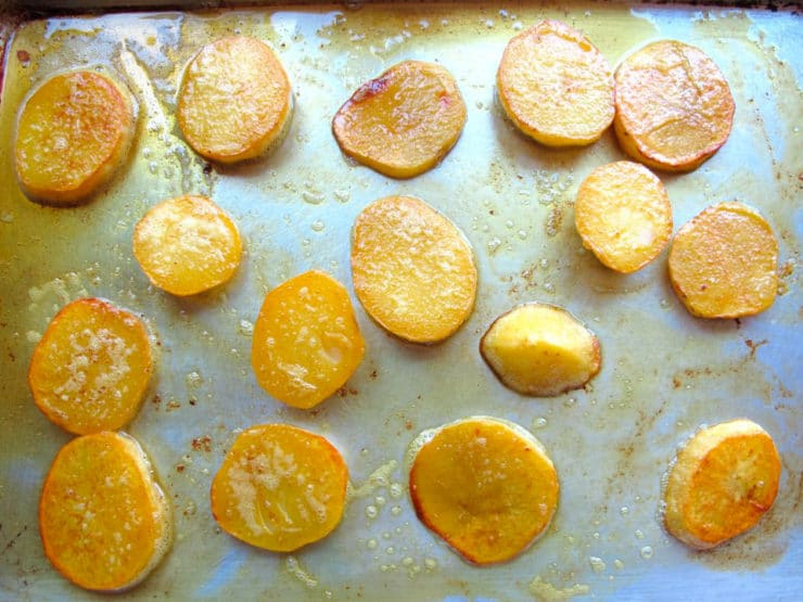 Baking potato slices on a baking sheet.