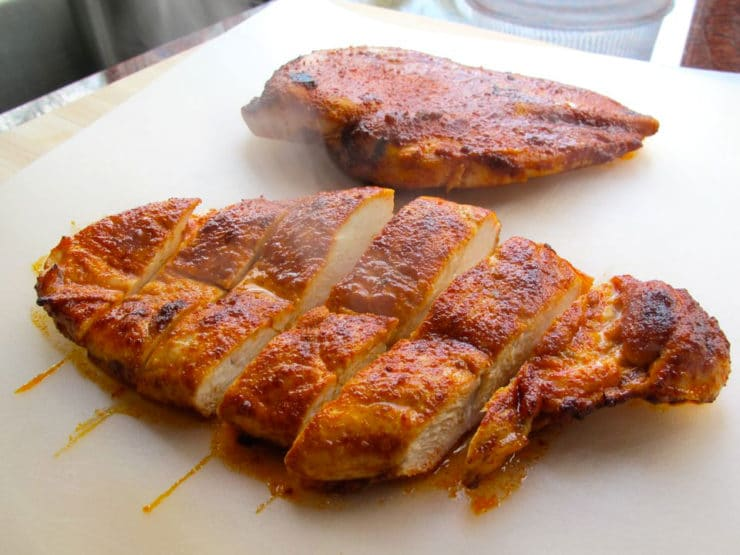 Paprika chicken breasts sliced on a cutting board.