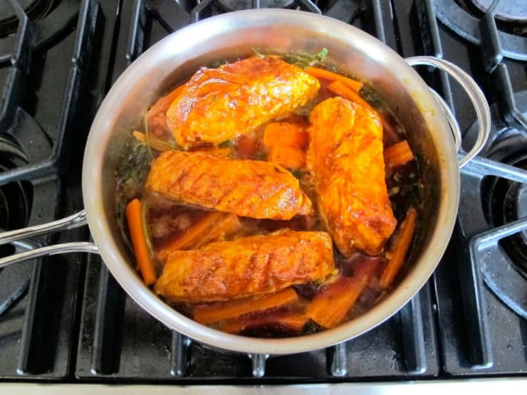 Fish fillets over carrots with liquid reduced down.