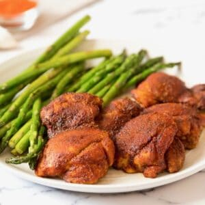 Horizontal Crop - Smoked Paprika Chicken Thighs with boneless skinless thighs, roasted asparagus in background, on a white plate on a white marble countertop, dish of smoked paprika and garlic cloves in background.