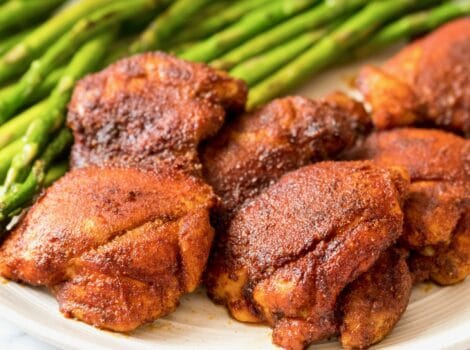 Square Crop - Smoked Paprika Chicken Thighs with boneless skinless thighs, roasted asparagus in background, on a white plate on a white marble countertop.