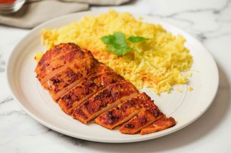 Horizontal shot - Smoked Paprika Chicken Breast with boneless skinless breast sliced, saffron rice garnished with cilantro in background, on a white plate with white marble background.