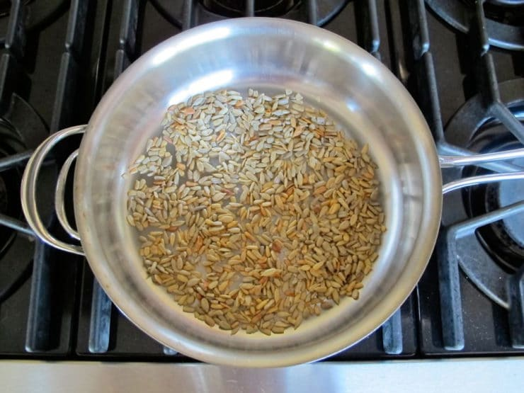 Dry toasting sunflower seeds in a skillet.