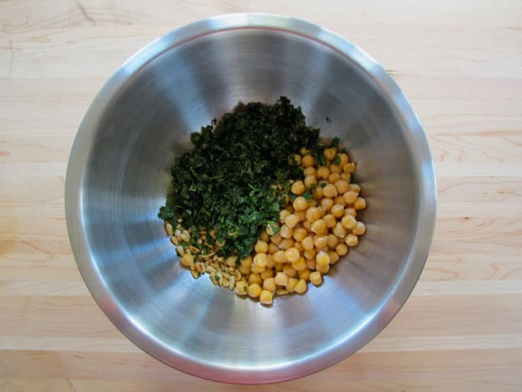 Garbanzo beans and cilantro in a mixing bowl.