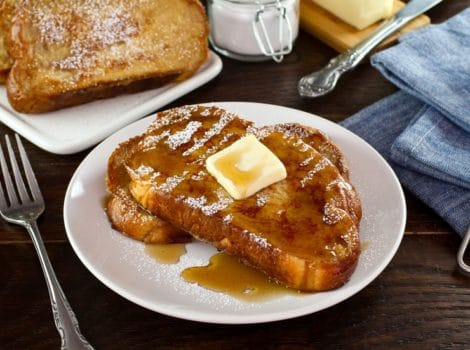 Front angle shot of Challah French Toast with butter, powdered sugar and maple syrup on a white plate with fork, placed on wooden table with cloth napkin. Powdered sugar and plate of French Toast in background.