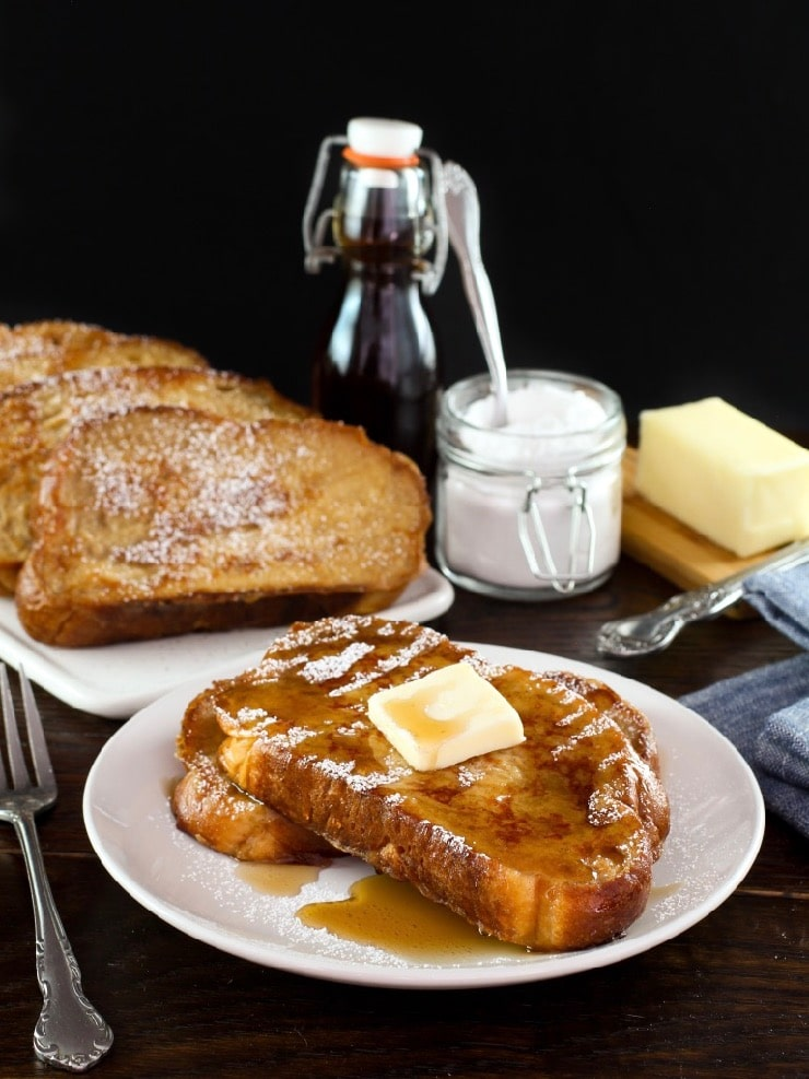 Vertical shot of Challah French Toast topped with pat of butter of maple syrup on a plate, platter of French toast, powdered sugar, bottle of maple syrup and stick of butter in background.
