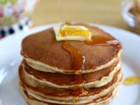 Close up of pancakes with butter and maple syrup on white plate.
