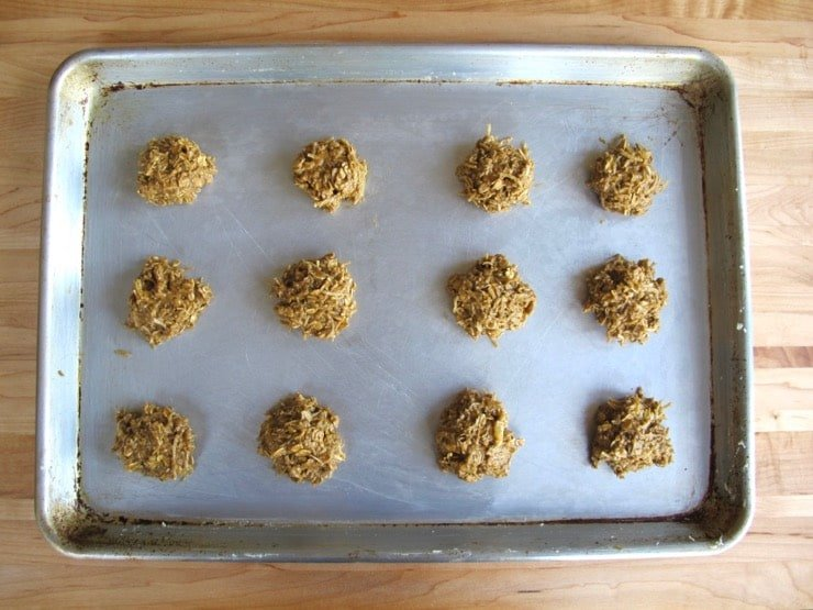 Molasses cookie dough formed into cookies on baking sheet.