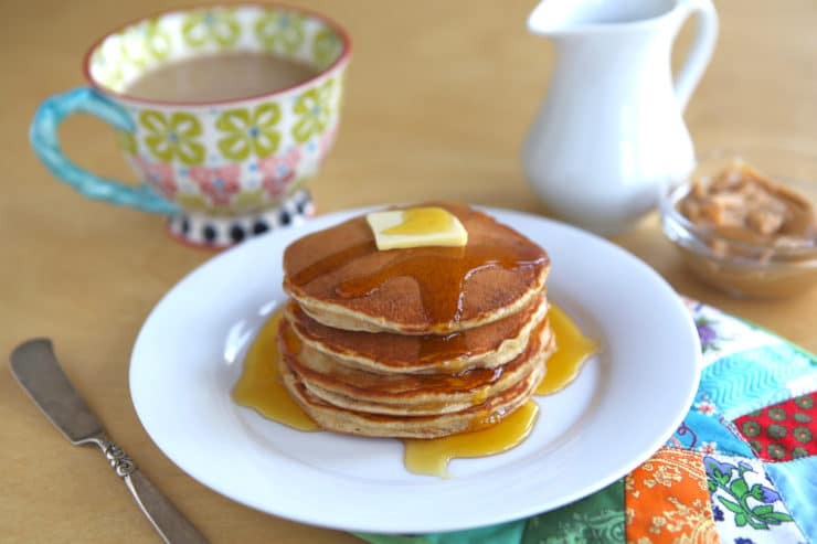 Peanut butter pancakes on white plate with butter and maple syrup, served with coffee.