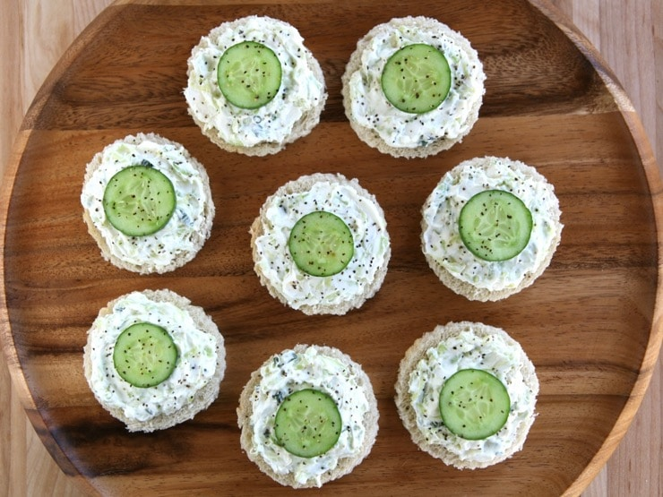 Overhead view - platter of cucumber rye open faced finger sandwiches, crustless, with pepper on a wooden background.