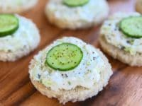 Cucumber rye open faced finger sandwich, crustless, with pepper on a wooden background.