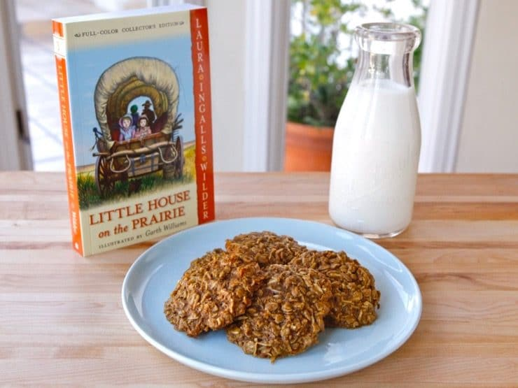 Wide shot - plate of 4 molasses cookies with Little House on the Prairie book and bottle of milk in background.