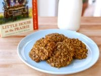 Plate of 4 molasses cookies with Little House on the Prairie book and bottle of milk in background.