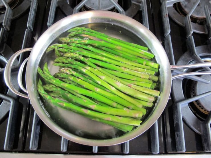 Asparagus in boiling water in a saucepan.
