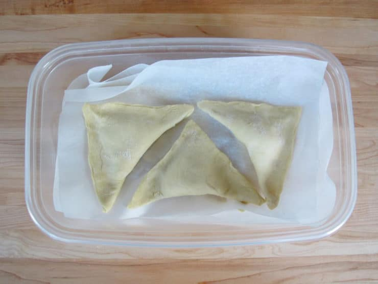 Freeze unbaked bourekas in layers of parchment.
