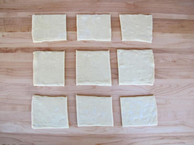 Puff pastry cut into nine squares.