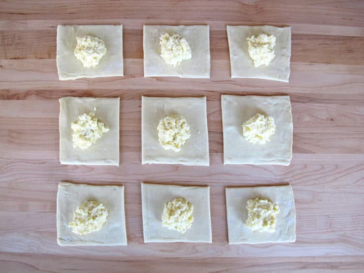 Cheese filling placed in center of puff pastry squares.