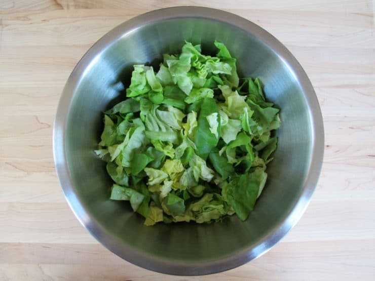 Torn butter lettuce in a large bowl.