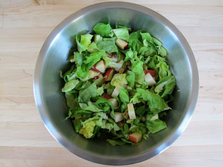 Fruit and lettuce tossed in a large bowl.