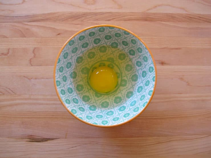 Single egg cracked, uncooked, in small decorative bowl on wooden cutting board.