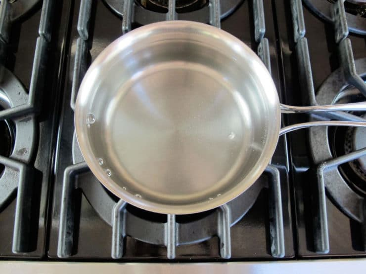 Saucepan with lightly simmering water on stovetop.