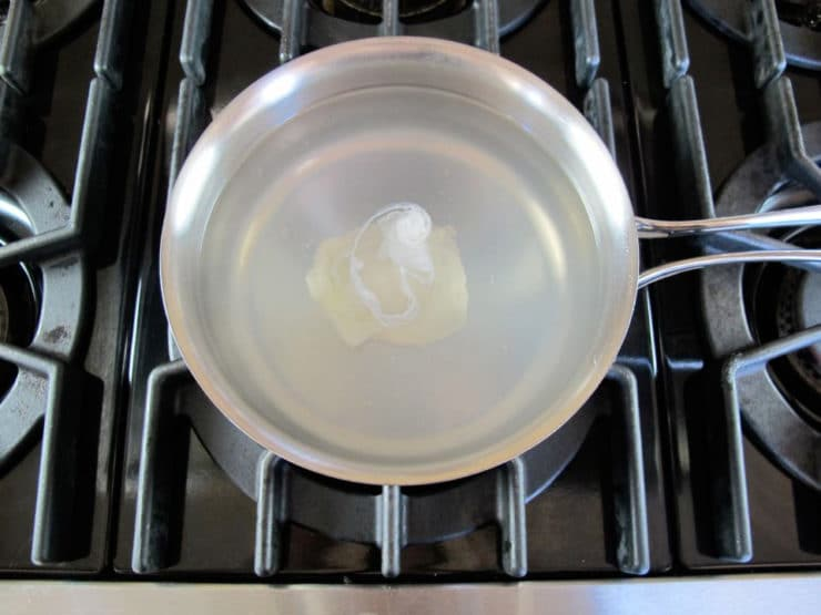 Single poached egg in center of saucepan with lightly simmering water on stovetop.