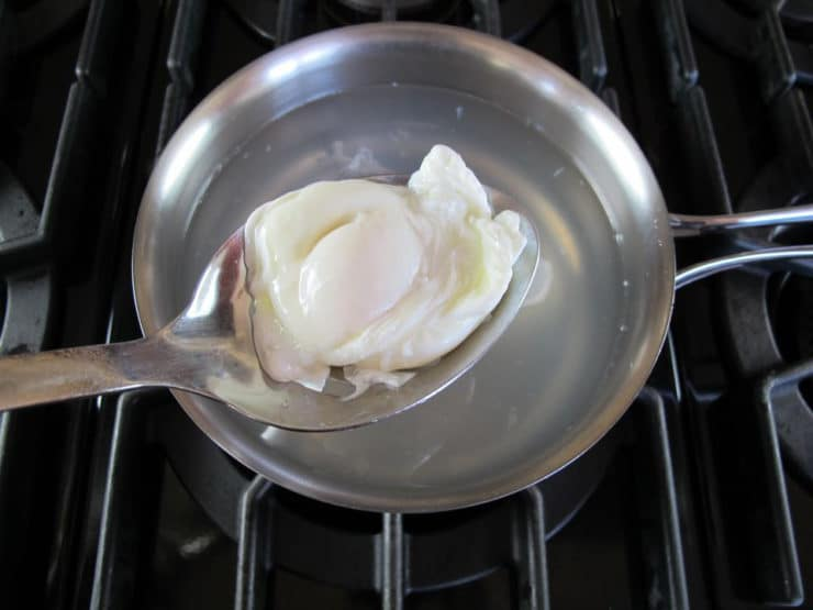 Single poached egg held in slotted spoon over saucepan with lightly simmering water on stovetop.