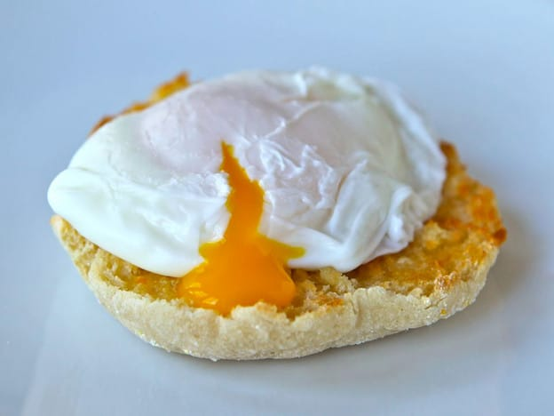 Poached egg on toasted English muffin broken with yolk dripping out.