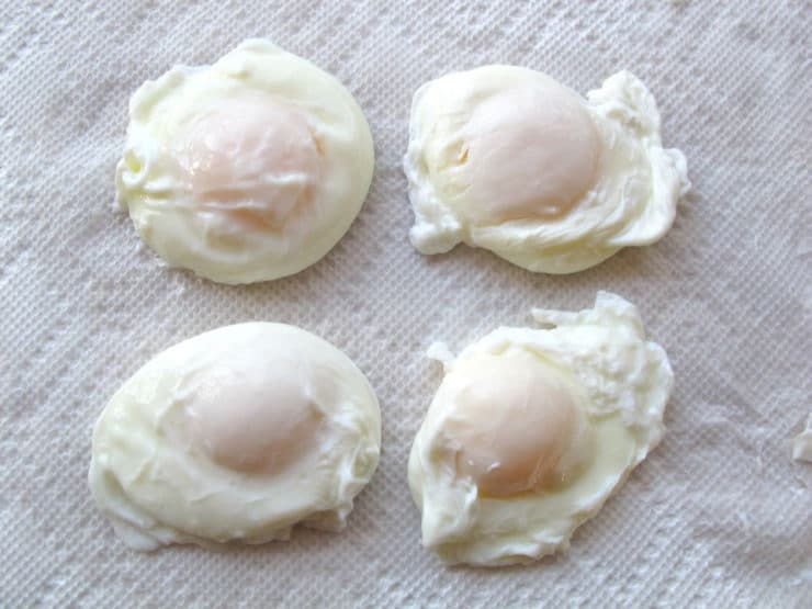 Four poached eggs on paper towel.