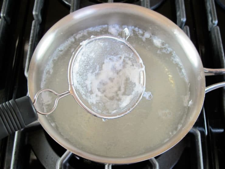 Mesh strainer collecting strands of egg from saucepan with simmering water on stovetop.
