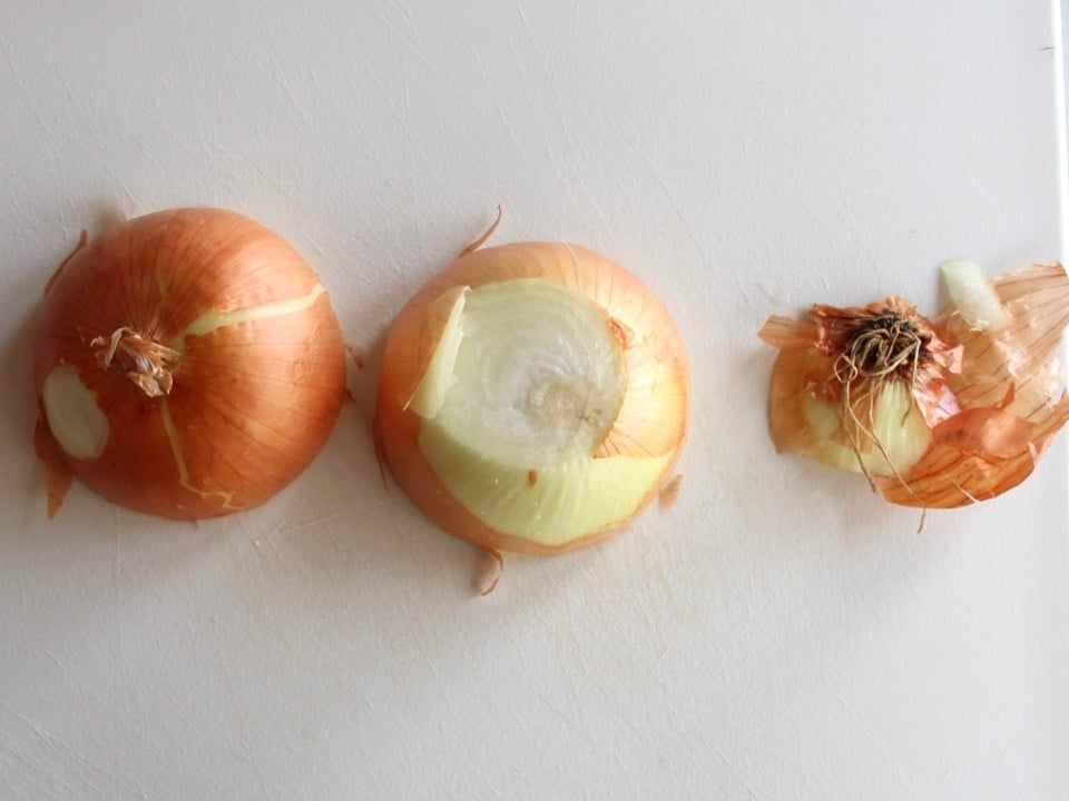 Yellow onion sliced in half on white cutting board, root end removed.