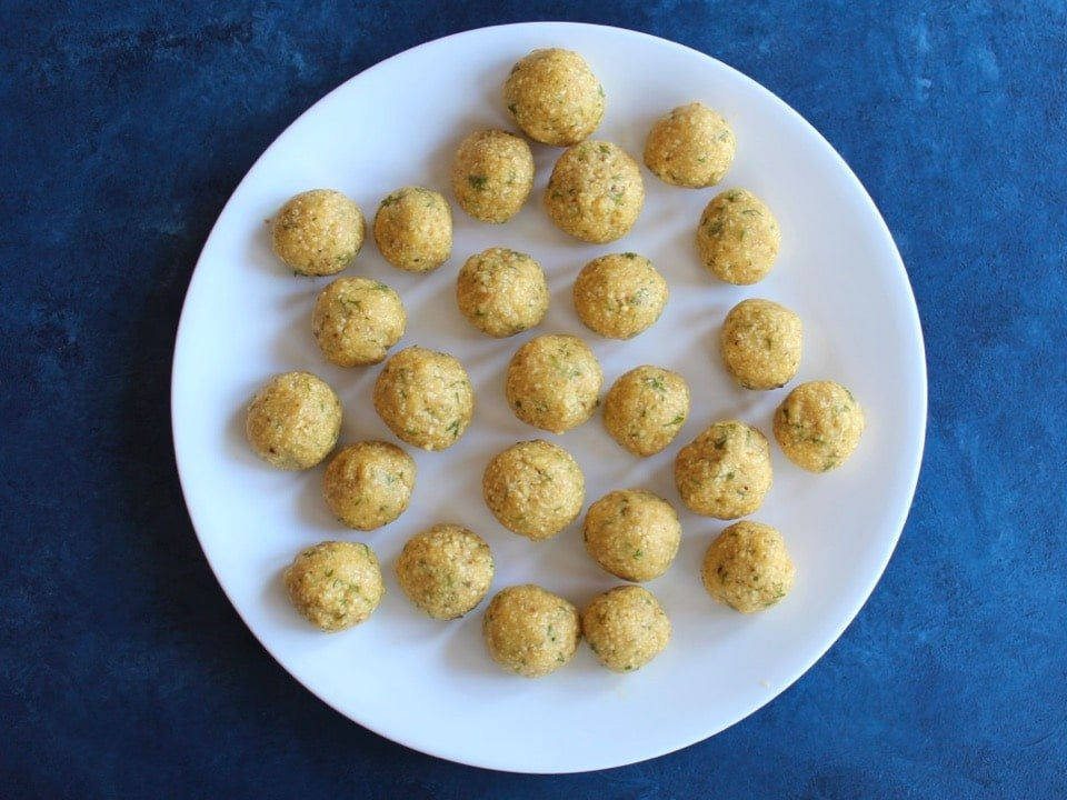 A plate of uncooked, rolled matzo balls, about 24 balls.