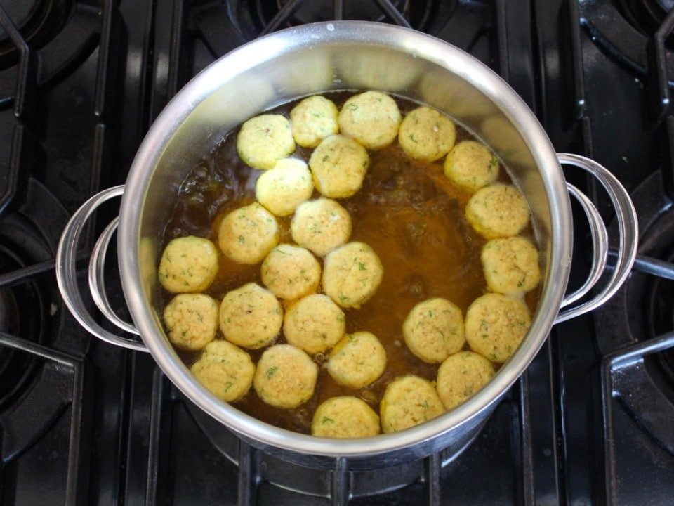 Overhead view of floater matzo balls starting to cook on top of a pot of simmering broth on stovetop.