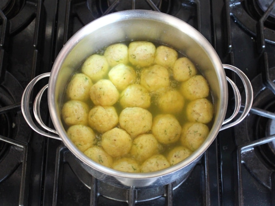 Fluffy, light matzo balls floating at the top of a pot on stovetop.