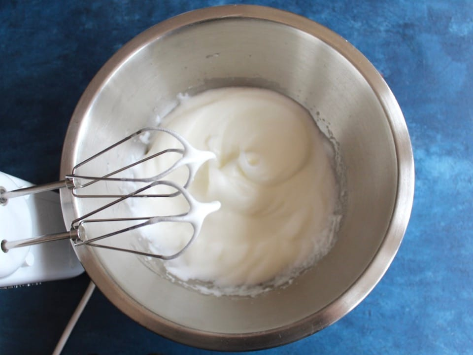Egg whites whipped to a white frothy texture with electric mixer beaters in a stainless bowl on a blue countertop.