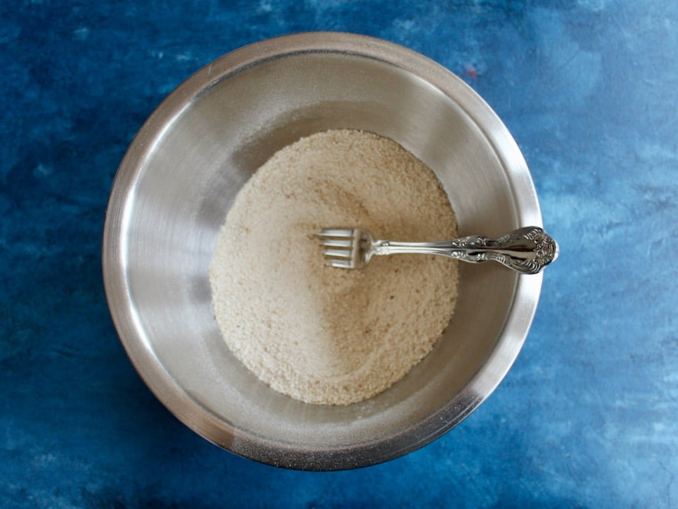 Dry matzo meal and matzo ball ingredients being stirred with a fork in a stainless bowl on a blue countertop.