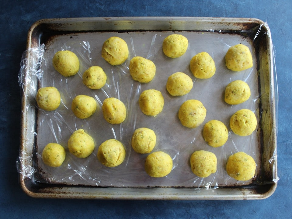 Matzo balls on a plastic wrap-lined baking tray, ready for freezing.