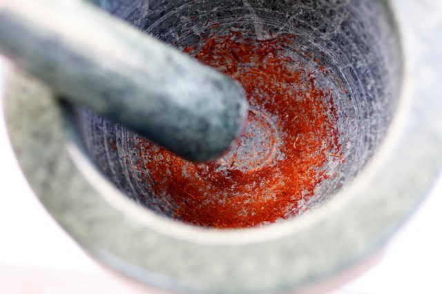 Grinding saffron with mortar and pestle.