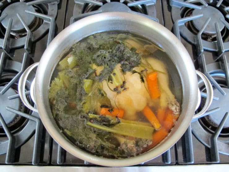 Whole chicken simmering in a pot.