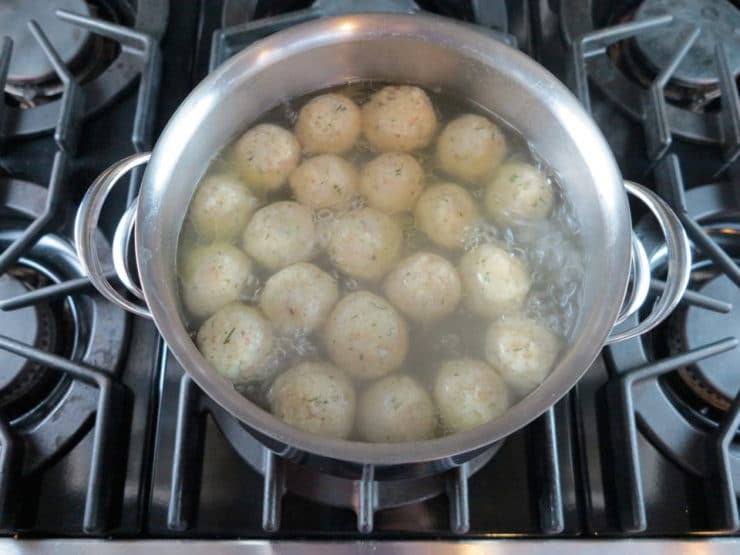 Matzo balls cooking in chicken stock.