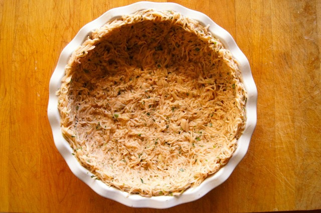 Shredded potatoes pressed into a pie plate.