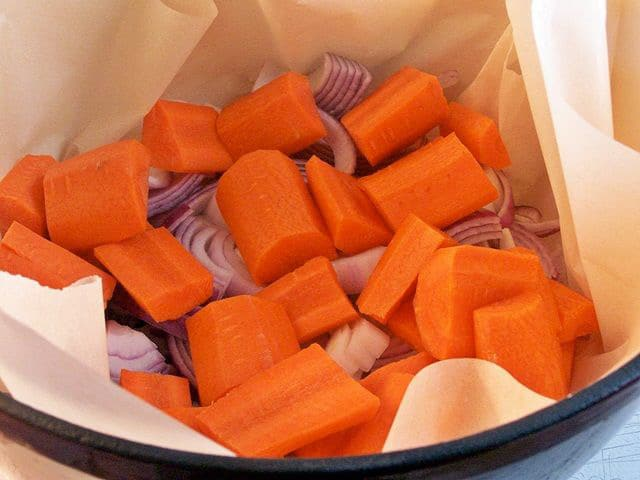 Diced carrots in a parchment lined Dutch oven.