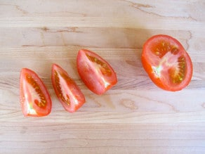Tomato half and three tomato quarters on cutting board.