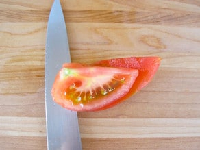 Knife removing pulp and seeds from skin of tomato quarter.