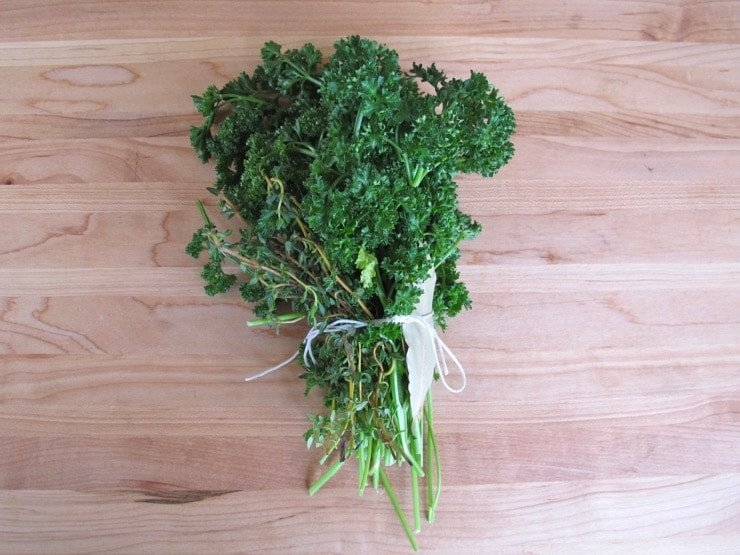 Bundle of herbs tied with string on wooden cutting board.