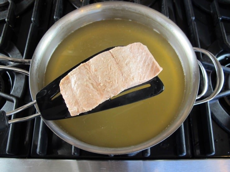 Salmon fillet poached on spatula held above a pot of Court Bouillon - Steaming hot, barely boiling, on stovetop.