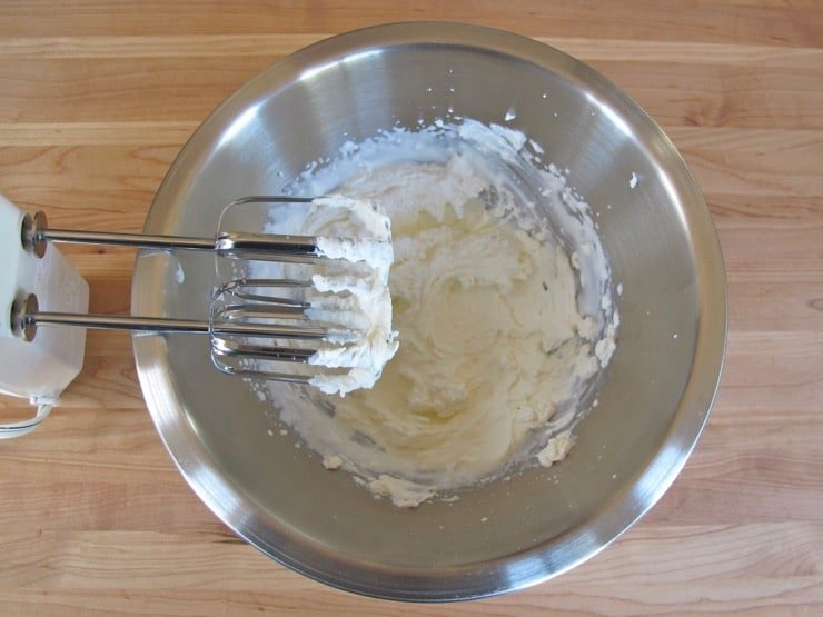 Whipping cream for Mousseline Sauce in stainless steel bowl with electric beaters on wooden background.